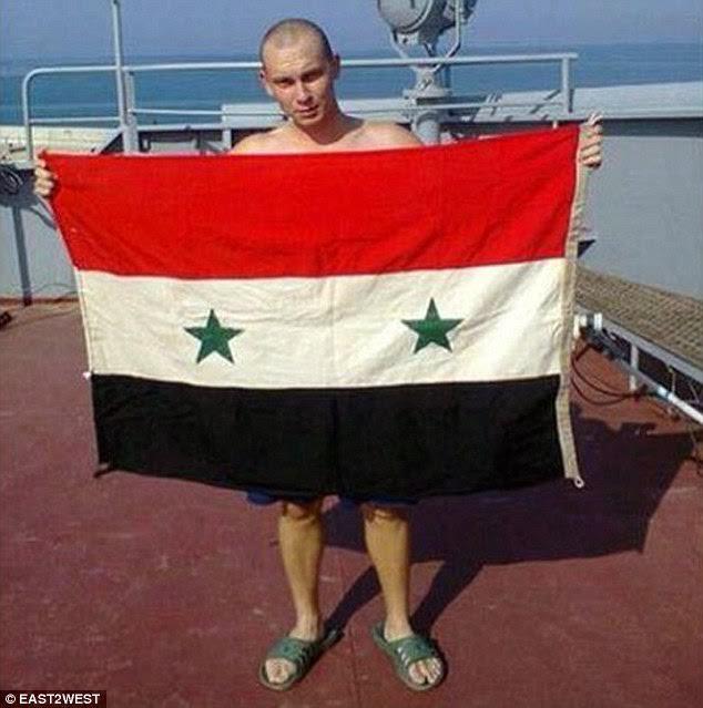 Militar rus cu steagul Siriei, pe o navă de război